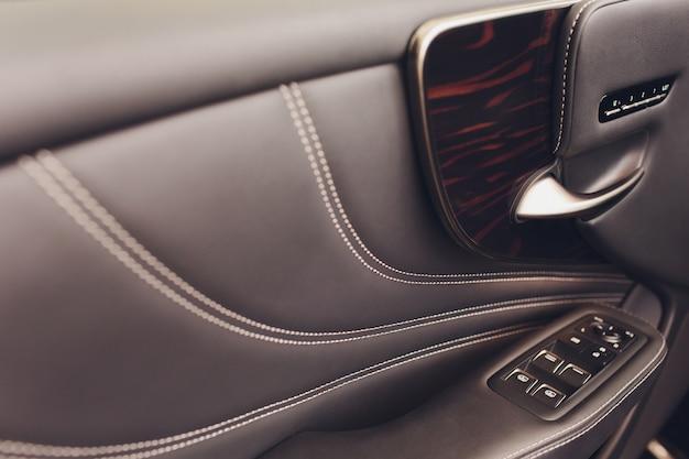 窓のコントロールと調整を備えたドアハンドルの車の革の内部の詳細。車の窓のコントロール。