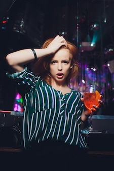 手でドリンクを飲みながら夜のクラブで踊る幸せな女。