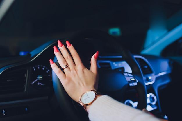 現代の高級車を運転するステアリングホイールに女性の手。コンセプト女性運転。運転中のステアリングホイールを握って手。車の中。車の詳細。