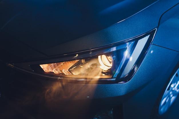 В гараже автомобильного салона, центр фар автомобиля очень близко, включение, выключение, проверка размеров передних фар