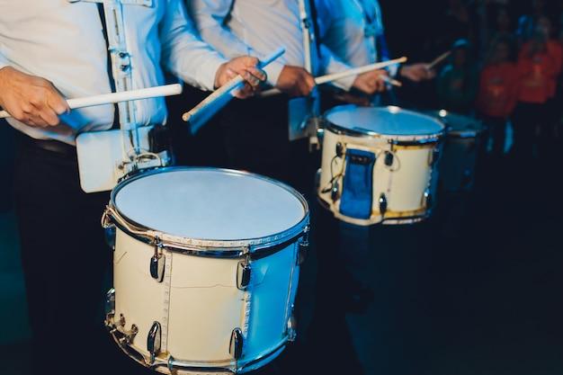 Неузнаваемый мужчина марширует во время игры на барабане на барабане.