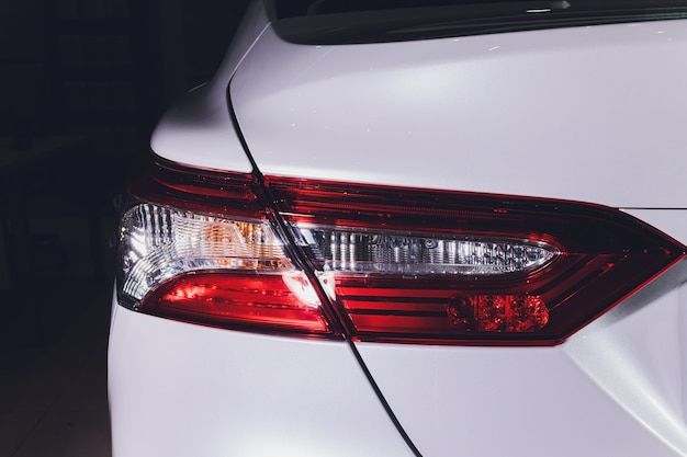 ウォッシュワックス後の白いペンキの反射とモダンで豪華なスポーツカーのテールライト詳細のクローズアップ。スーパーカーのブレイクライトの背面図。カーディテーリングと塗装保護のコンセプト