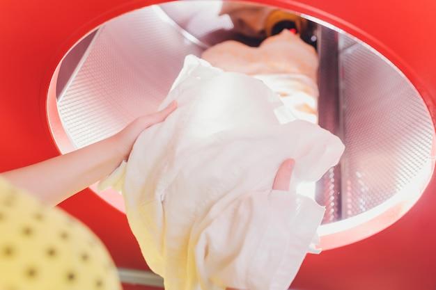 ドライクリーナーで洗濯機に洗濯物をロードする手。