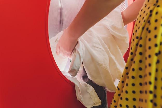 Руки для загрузки белья в стиральную машину в химчистке.