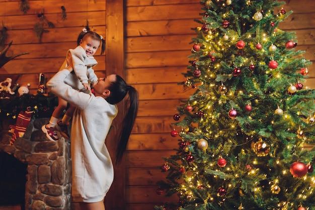メリークリスマスとハッピーホリデー陽気なママとかわいい娘の女の子が贈り物を交換します。親と小さな子供が室内のクリスマスツリーの近く楽しんで。部屋にプレゼントがある愛情のある家族。