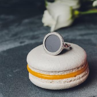 繊細なイヤリングは、表面に金色のリングが付いたピンクのマカロンにあります