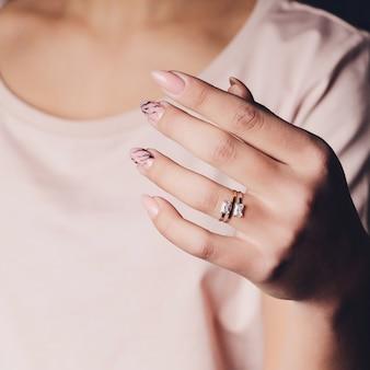 ダイヤモンドの指輪を示す女性の手のクローズアップ。彼女は従事しています。