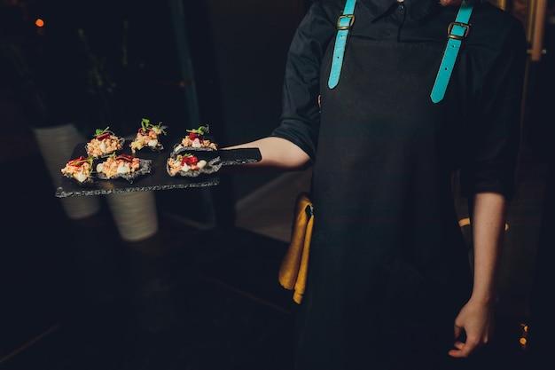 Официант с подносом закусок на банкет или прием. питание шведский стол на вечеринке.