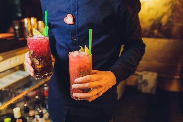 Прохладный напиток коктейль в руках официанта.