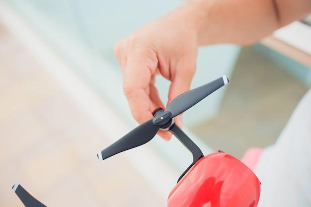 Красный дрон ловить контроль руками человека. выкладывает пропеллеры