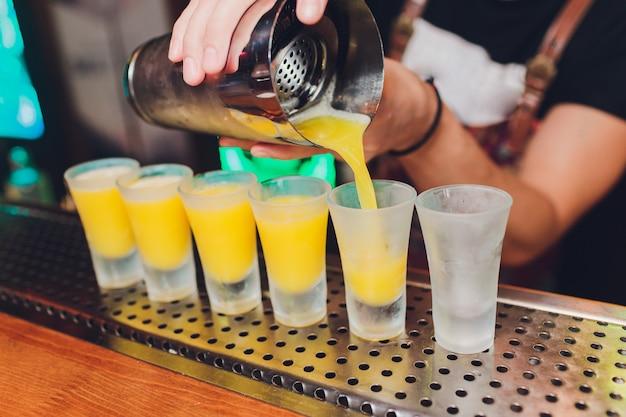 バーテンダーが強いアルコール飲料をバーの小さなグラスに注いでいます。