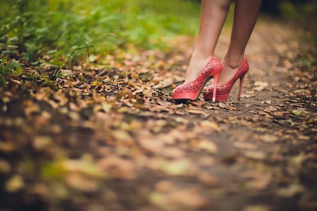 秋の紅葉の革のブーツの足。自然の中を歩く足の靴