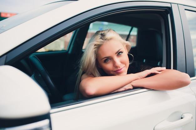 自動車ショールームで新しい高価な購入で喜んで幸せな笑顔の女性。白い折りたたみ式トップカーのドアに座っている美しいお客様。