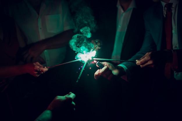 Праздник фон с бенгальскими огнями. молодые друзья держа света бенгалии, крупный план, селективный фокус. день рождения или праздник зимних праздников