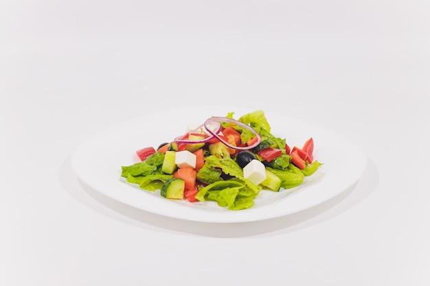 白い背景に分離された新鮮野菜のサラダ。