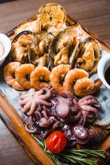 焼きイカ、エビ、ムール貝のソース、木の板