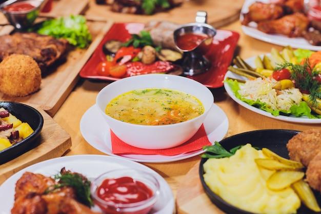 グリルソーセージ、トルティーヤラップ、ビール飲料、素朴なスタイルの木製テーブルにさまざまな料理のディナーテーブル。
