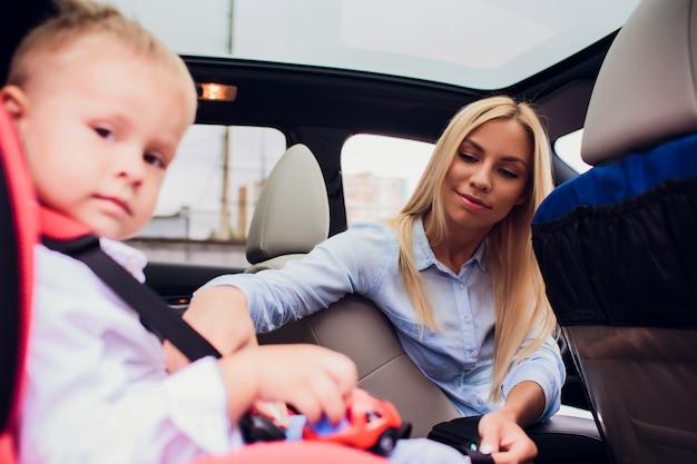 家族、交通機関、遠征、人々のコンセプト-車の安全シートベルトで子供を固定する幸せな女