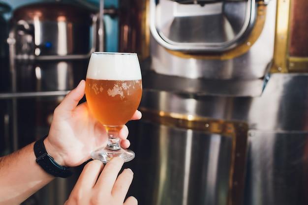オクトーバーフェストフェスティバル。新鮮な醸造ビールの試飲。ビールはグラスにクラフトビールが入っています。醸造所のコンセプト。マグカップのビールを持つ男。アルコール。男性の醸造家はビールとグラスを保持しています。オクトーバーフェスト。バーマン。ブリューワー。