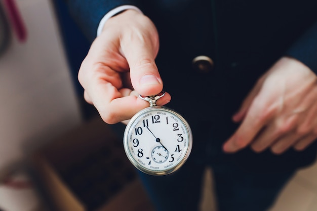 レトロな懐中時計と手のクローズアップ。