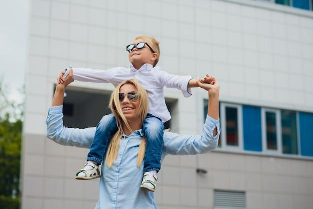 Молодая мать с ее маленьким мальчиком на открытом воздухе на стеклянной стене