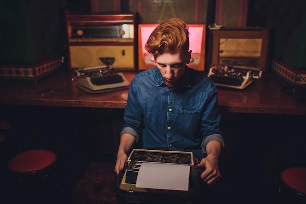 若い男が古いタイプライターで書きます。暗い照明、レストラン、モダンな服、古い作家の習慣