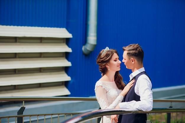 街を歩いて新郎新婦の結婚式の日、結婚の概念。都市の背景に新郎新婦。式の日に階段に行く若いカップル。