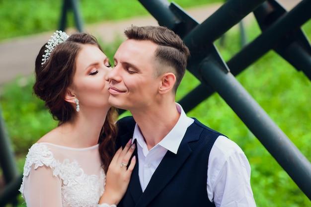 美しい花嫁と花婿を受け入れ、彼らの結婚式の日にキスします。
