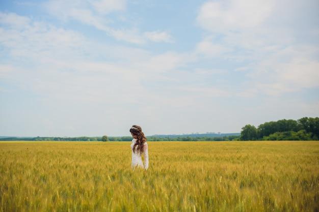 Невеста на открытом воздухе в утро, окруженное золотым солнечным светом.