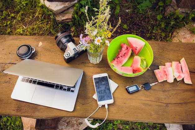 木製の背景にノートパソコンと夏の休暇のアイテム。上からの眺め