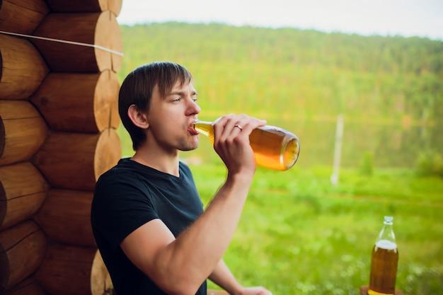 プールの近くの戸外でガラスからビールを飲む男性を閉じます。アルコールとレジャーのコンセプトです。