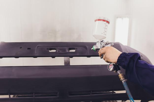 自動車用塗料。自動車修理工場で車を塗装するメカニック。