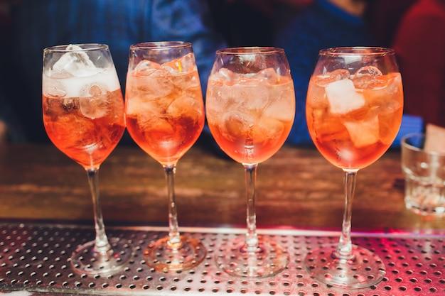 Кампари тоник алкогольный коктейль с красным горьким, тоник, лайм и лед. старая предпосылка деревянного стола, инструменты бара, селективный фокус. все названия относятся к коктейлям, а не товарным знакам.