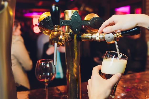 オクトーバーフェストに会います。タップで大きなラガービールを注ぐバーテンダーの手