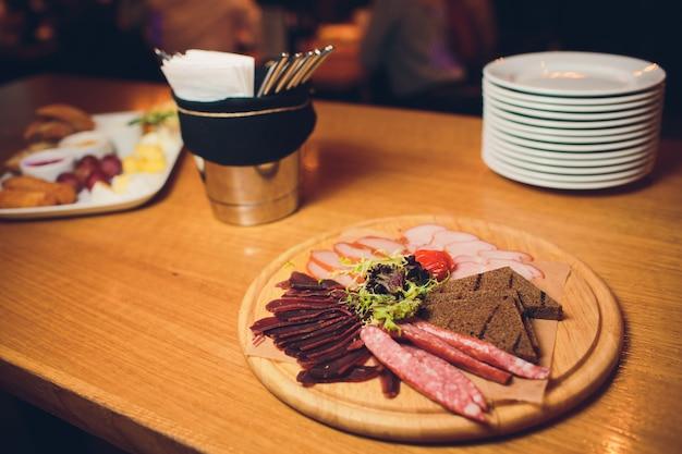 Деревянный поднос с тремя видами колбас.