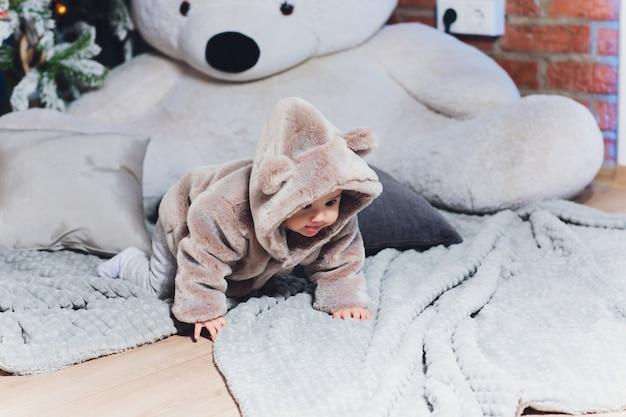 床にクマとスーツを着たかわいい赤ちゃん。