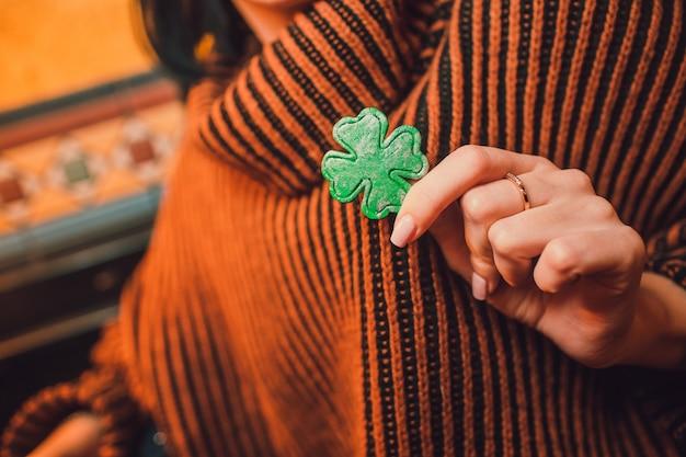 緑のクローバーのネックレスを持っている男性の手。聖パトリックの日の準備。