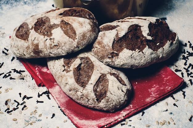 Нарезанный черный хлеб на старой деревянной доске.