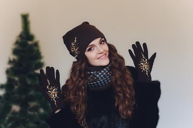 Рождественская девочка в вязаной теплой шапке и варежках, изолированных на сером