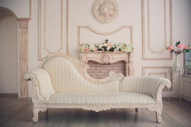 ヴィンテージ家具、美しい白いソファと花瓶に花が咲く明るい春のスタジオのあるインテリア。写真撮影のための白とピンクの花を持つスタジオの白いインテリア。