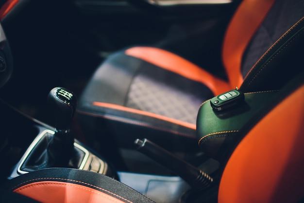ワイヤレスキー点火の車内のクローズアップ。黒の穴あき革のインテリアの車のキーリモート。カーディテーリング。キーをクローズアップ。