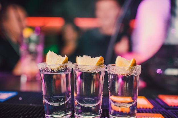Аперитив с друзьями в баре, пять бокалов алкоголя с закусками из лайма и фисташки, соль и перец чили для украшения. текила, водка, виски, ром. выборочный фокус и копирование пространства.