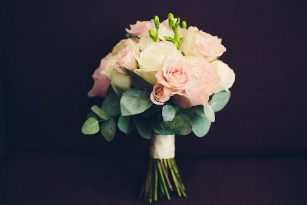 黒の背景に白とピンクのバラの美しいウェディングブーケ。