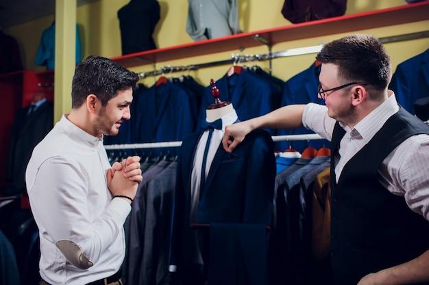 男は店でスーツを買っています