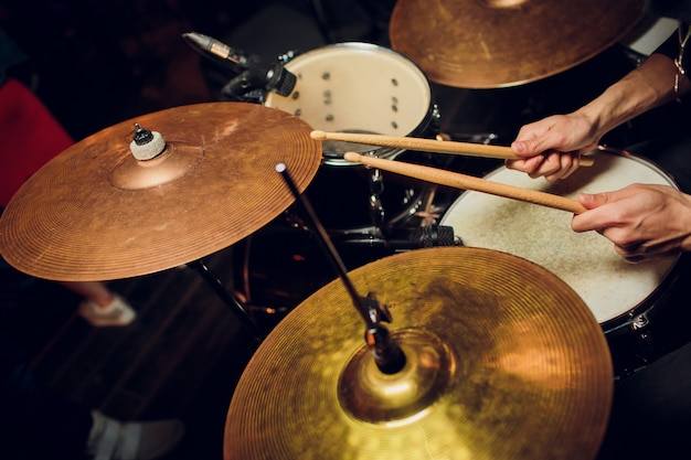 Живая музыка в старинном стиле, барабанщик играет с барабанными палочками на рок-барабане