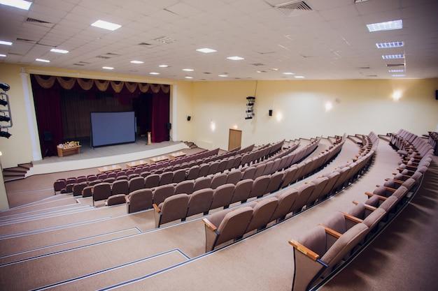 Конференц-зал с потолочными светодиодными светильниками, рядными коричневыми стульями, со сценой и пустым экраном для деловой встречи, конференции