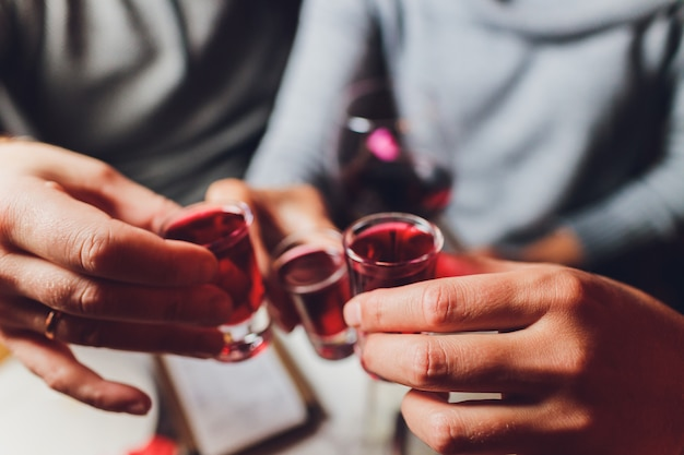 Крупным планом выстрел из группы людей, чокающихся с вином или шампанским в передней