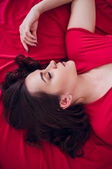 黒い下着姿の美しい妊婦が灰色のベールに横たわっています。ベッドは新鮮な花で飾られています。女の子はブロンドの髪をしています。上からの眺め。