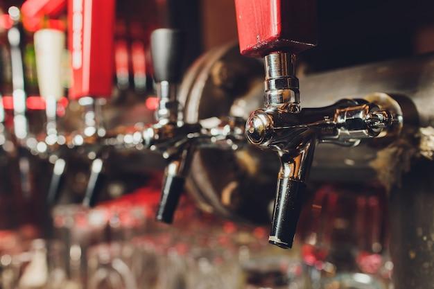 びんおよびビールを分配するための器具が付いている棒カウンター。バーでビールを分配するための装置。パブ。レストランのバー。レストランでビールを分配するための装置。