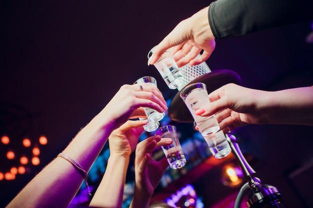 ドリンクをしがみつく人々が一緒に乾杯の手を上げる